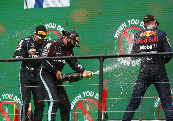 Race winner Mercedes driver Lewis Hamilton of Britain, centre, sprays champagne at the podium with second placed Mercedes driver Valtteri Bottas of Finland, left, and third placed Red Bull driver Max Verstappen of the Netherlandsafter the Formula One Portuguese Grand Prix at the Algarve International Circuit in Portimao, Portugal, Sunday, Oct. 25, 2020. (Rafael Marchante, Pool via AP)
