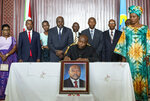 FILE - In this Saturday, June 13, 2020 file photo, Burundi's president-elect Evariste Ndayishimiye, center, accompanied by his wife Angeline Ndayubaha, right, signs the book of condolences, above a photograph of the late President Pierre Nkurunziza, at the presidential palace in Bujumbura, Burundi. A new report released Thursday, Sept. 17, 2020 by the United Nations commission of inquiry on Burundi sees little optimism in the government of new President Evariste Ndayishimiye, saying it is