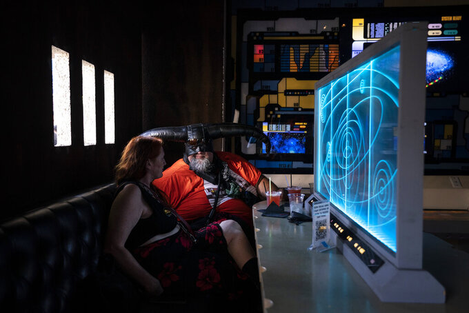 Candice Tate, left, and her boyfriend Brandon Daniels celebrate Star Wars Day at Scum and Villainy Cantina, a geek bar located on Hollywood Boulevard in Los Angeles, Tuesday, May 4, 2021. California has the lowest infection rate in the country. Los Angeles County, which is home to a quarter of the state's nearly 40 million people and has endured a disproportionate number of the state's 60,000 deaths, didn't record a single COVID-19 death Sunday or Monday, which was likely due to incomplete weekend reporting but still noteworthy. (AP Photo/Jae C. Hong)