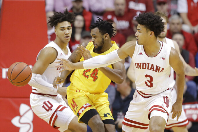 Maryland's Donta Scott (24) and Indiana's Justin Smith (3) eye the ball during the first half of an NCAA college basketball game, Sunday, Jan. 26, 2020, in Bloomington, Ind. (AP Photo/Darron Cummings)