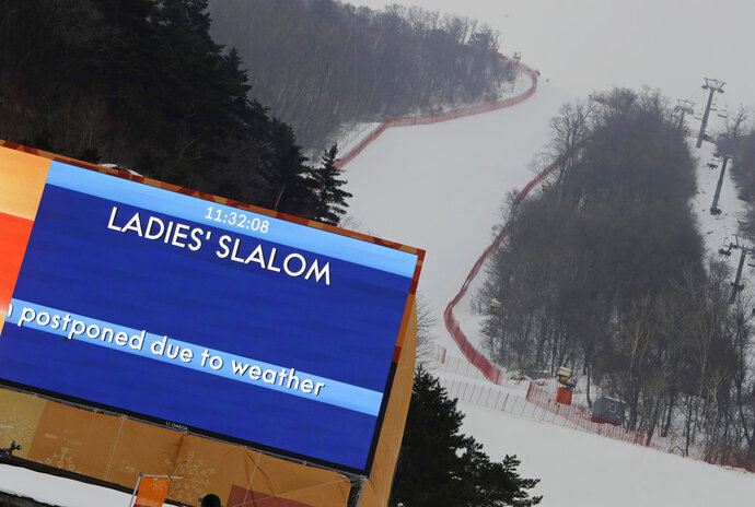 A sign says that the women's slalom has been canceled due to weather at Yongpyong alpine center at the 2018 Winter Olympics in Pyeongchang, South Korea, Wednesday, Feb. 14, 2018. (AP Photo/Michael Probst)
