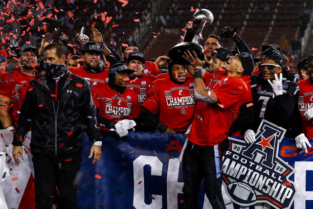 Cincinnati quarterback Desmond Ridder holds the trophy following the American Athletic Conference championship NCAA college football game against Tulsa, Saturday, Dec. 19, 2020, in Cincinnati. Cincinnati won 27-24. (AP Photo/Aaron Doster)