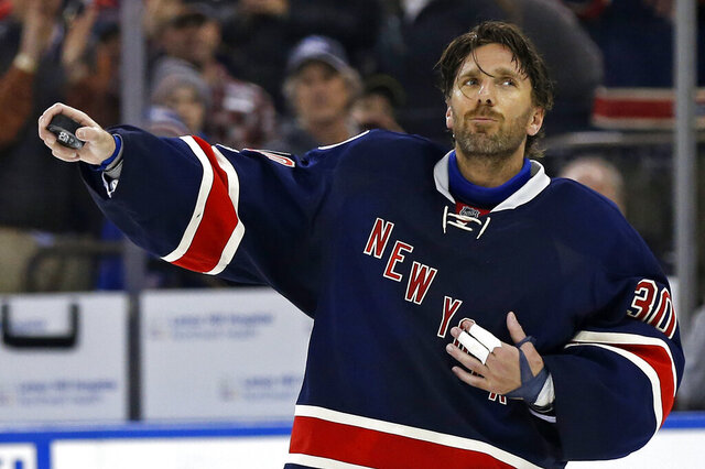 FILE - In this Feb. 11, 2017, file photo, New York Rangers goalie Henrik Lundqvist celebrates his 400th career win, after an NHL hockey game against the Colorado Avalanche, in New York. The New York Rangers have bought out the contract of star goaltender Henrik Lundqvist. The Rangers parted with one of the greatest netminders in franchise history on Wednesday, Sept. 30, 2020, when they paid off the final year of his contract. (AP Photo/Adam Hunger, File)