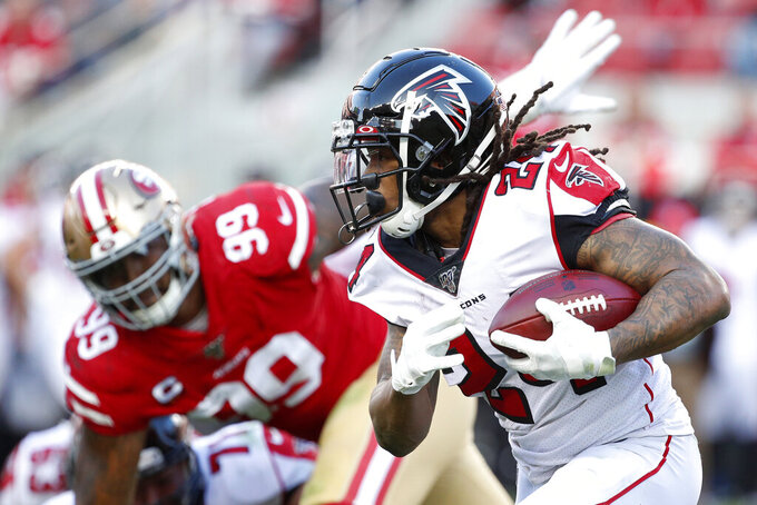 Atlanta Falcons running back Devonta Freeman (24) runs in front of San Francisco 49ers defensive tackle DeForest Buckner (99) during the second half of an NFL football game in Santa Clara, Calif., Sunday, Dec. 15, 2019. (AP Photo/Josie Lepe)