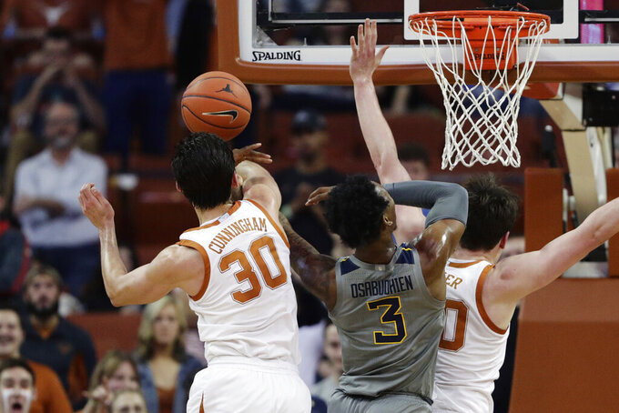 West Virginia forward Gabe Osabuohien (3) is blocked by Texas forward Brock Cunningham (30) as he tries to score during the second half of an NCAA college basketball game, Monday, Feb. 24, 2020, in Austin, Texas. (AP Photo/Eric Gay)