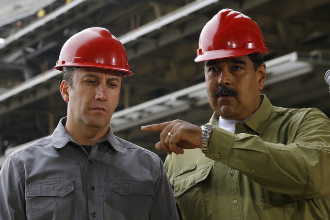 FILE - In this May 19, 2018 file photo, Venezuela's President Nicolas Maduro, right, and Vice President Tareck El Aissami tour La Rinconada baseball stadium that is under construction on the outskirts of Caracas, Venezuela. President Maduro on Monday, April 27, 2020, named El Aissami , a powerful ally sanctioned by the U.S. as a drug kingpin along with a cousin of the late socialist leader Hugo Chávez, to revamp Venezuela's oil industry amid massive gasoline shortages. (AP Photo/Ricardo Mazalan, File)