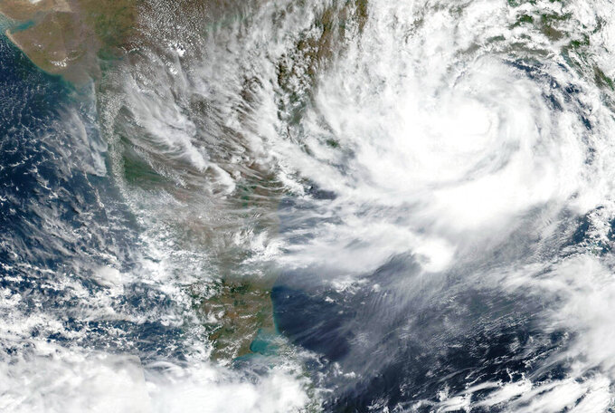 This Tuesday, May, 25, 2021, satellite image provided by NASA shows Cyclone Yaas approaching India's eastern coast. Tens of thousands of people are being evacuated from low-lying areas of two Indian states to escape the strong cyclone barreling toward the eastern coast. Yaas is expected to make landfall Wednesday in West Bengal and Odisha states. It comes amid a coronavirus surge, complicating India's efforts to deal with both. (NASA Worldview, Earth Observing System Data and Information System (EOSDIS) via AP)