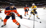 Nashville Predators' Kyle Turris (8) and Edmonton Oilers' Kris Russell (4) battle for the puck during third period NHL hockey action in Edmonton, Alberta, Tuesday, Jan. 14, 2019. (Jason Franson/The Canadian Press via AP)