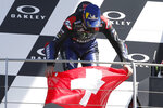 First placed, Yamaha rider Fabio Quartararo, of France, holds the Swiss flag to honor 19 years-old Swiss rider Jason Dupasquier, during the podium ceremony at the end of the Motogp Grand Prix of Italy at the Mugello circuit, in Scarperia, Italy, Sunday, May 30, 2021. Dupasquier died Sunday after being hospitalized Saturday, at the Florence hospital, following his crash during the qualifying practices of the Moto3. (AP Photo/Antonio Calanni)