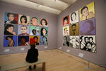 In this photo taken Wednesday, May 15, 2019, a woman views commissioned portraits from 1968-1987 at the exhibition,