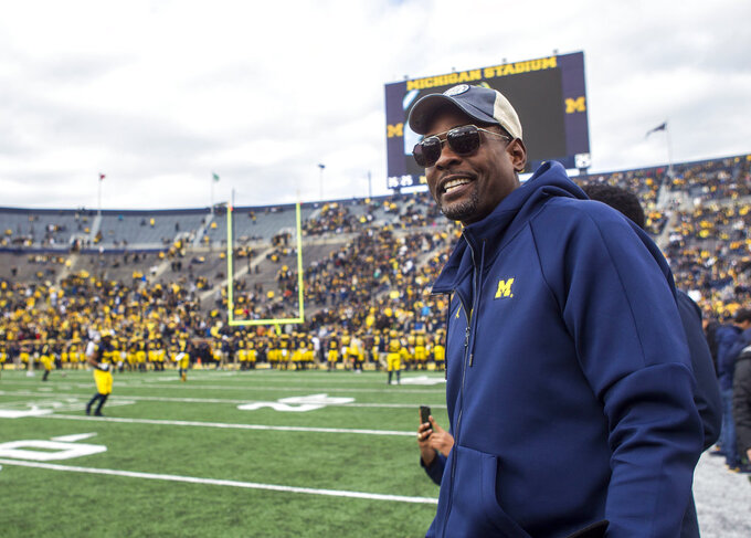 Former Michigan basketball player Chris Webber, right, walks on the Michigan Stadium field prior to an NCAA college football game against Penn State in Ann Arbor, Mich., Saturday, Nov. 3, 2018. Michigan is making Webber an honorary captain for the game. (AP Photo/Tony Ding)