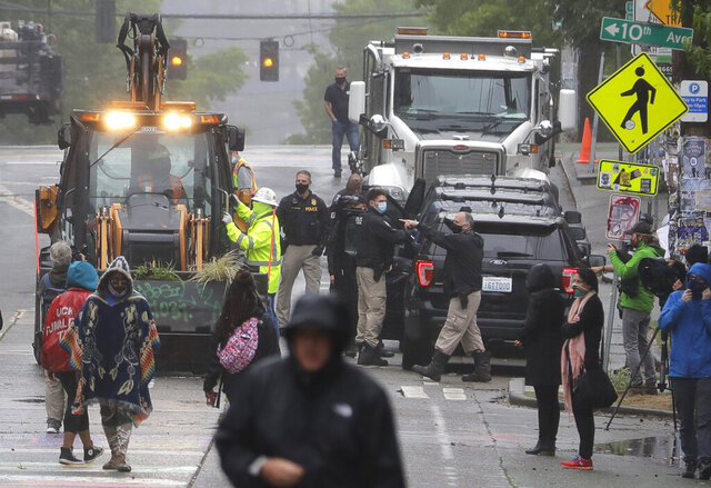Seattle Police, at right, look on as Department of Transportation workers remove barricades at the intersection of 10th Ave. and Pine St., Tuesday, June 30, 2020 at the CHOP (Capitol Hill Occupied Protest) zone in Seattle. Protesters quickly moved couches, trash cans and other materials in to replace the cleared barricades. The area has been occupied by protesters since Seattle Police pulled back from their East Precinct building following violent clashes with demonstrators earlier in the month. (AP Photo/Ted S. Warren)