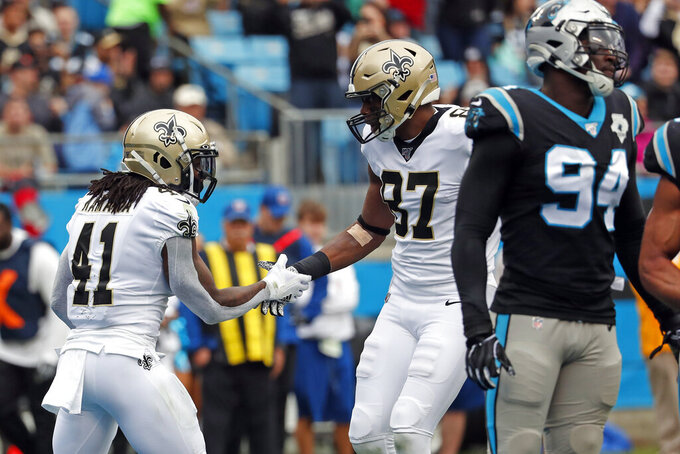 New Orleans Saints running back Alvin Kamara (41) and tight end Jared Cook (87) celebrate Kamara's touchdown against the Carolina Panthers during the first half of an NFL football game in Charlotte, N.C., Sunday, Dec. 29, 2019. (AP Photo/Gerry Broome)