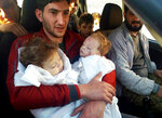 FILE -- In this April 4, 2017 file photo, Abdel Hamid al-Yousef, holds his twin babies who were killed during a suspected chemical weapons attack, in Khan Sheikhoun in the northern province of Idlib, Syria. Al-Yousef lost the twins, his wife and 16 other relatives in the poison gas attack that hit Khan Sheikhoun in April 2017. Determined to continue with his life, Al-Yousef remarried, and has an 11-month-old daughter. But tragedy keeps chasing the 31-year-old former shopkeeper as he recently fled a government assault on Idlib and the nonstop bombardment of Khan Sheikhoun. (Alaa Alyousef via AP, File)