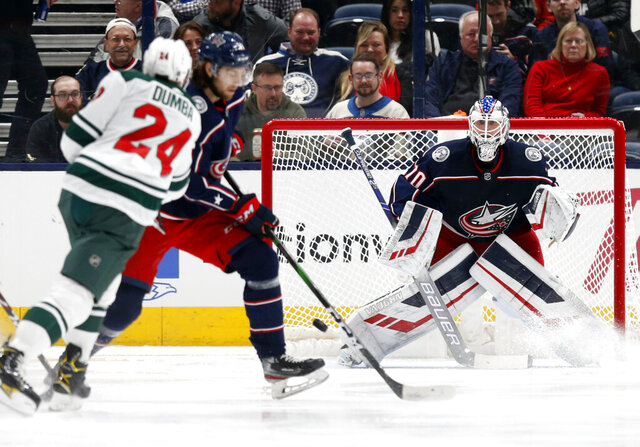 Columbus Blue Jackets goalie Joonas Korpisalo, right, of Finland, watches a shot by Minnesota Wild defenseman Matt Dumba, left, as Blue Jackets forward Kevin Stenlund, of Sweden, defends during the second period of an NHL hockey game in Columbus, Ohio, Friday, Feb. 28, 2020. (AP Photo/Paul Vernon)