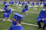 Graduating students practice socially distance by sitting far apart during a graduation ceremony at Millburn High School in Millburn, N.J., Wednesday, July 8, 2020. This week New Jersey saw the resumption of youth day camps, in-person summer school and school graduation ceremonies, capped at 500 people and required to be outside. (AP Photo/Seth Wenig)