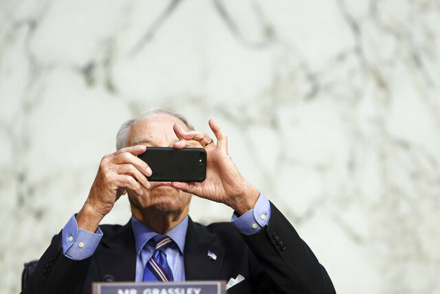 FILE - In this Monday, Oct. 12, 2020 file photo, Sen. Chuck Grassley, R-Iowa, uses his smartphone during a hearing on Capitol Hill in Washington. Researchers from NATO StratCom, a NATO-accredited research group based in Riga, Latvia, paid three Russian companies 300 euros ($368) to buy 337,768 fake likes, views and shares of posts on Facebook, Instagram, Twitter, YouTube and TikTok, including content from verified accounts of Senators Grassley and Chris Murphy. Both senators consented to participate. (Erin Schaff/The New York Times via AP, Pool)