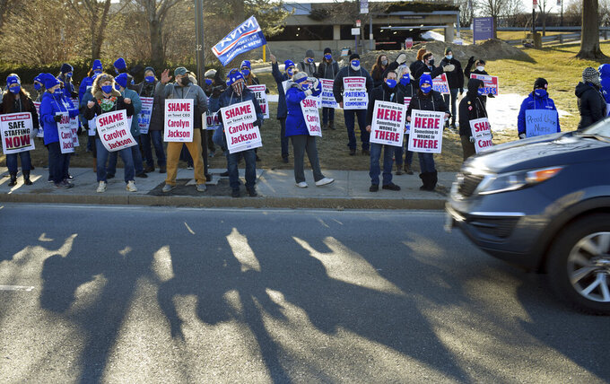 Saint Vincent nurses line Summer St. holding signs ahead of the planned rally on Sunday, March 7, 2021, in Worcester, Mass. (Christine Peterson/Worcester Telegram & Gazette via AP)