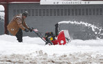 A maintenance man uses a snowblower to clear a sidewalk outside a condominium complex along Grant Street as a storm packing snow and high winds sweeps in over the region Tuesday, Nov. 26, 2019, in Denver. Stores, schools and government offices were closed or curtailed their hours while on another front, Thanksgiving Day travellers were forced to wrestle with snow-packed roads and flight delays or cancellations throughout the intermountain West. (AP Photo/David Zalubowski)