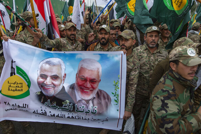 FILE - In this Saturday, Jan. 4, 2020 file photo, Iraqi militiamen march and chant anti U.S. slogans while carrying a picture of Soleimani, left and al-Muhandis, with Arabic that reads