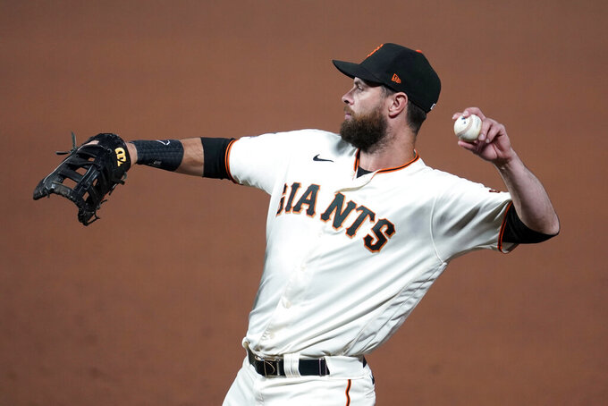 FILE- In this Sept. 22, 2020, file photo, San Francisco Giants' Brandon Belt throws the ball  during a baseball game against the Colorado Rockies in San Francisco. Belt got hit with quite a double-whammy that derailed his offseason: First, in January, he contracted the coronavirus only to immediately become ill again with mononucleosis. Gradually regaining his strength and stamina at last, the first baseman acknowledges he isn't sure he will be ready for opening day with the San Francisco Giants.  (AP Photo/Jeff Chiu, File)
