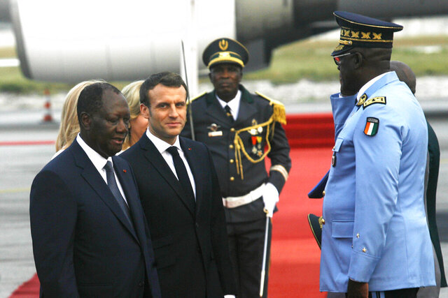 French President Emmanuel Macron is welcomed by President Alassane Ouattara upon arrival in Abidjan, Ivory Coast, Friday Dec. 20, 2019. Macron is in Ivory Coast for a three-day official visit.  (AP Photo/Diomande Ble Blonde)