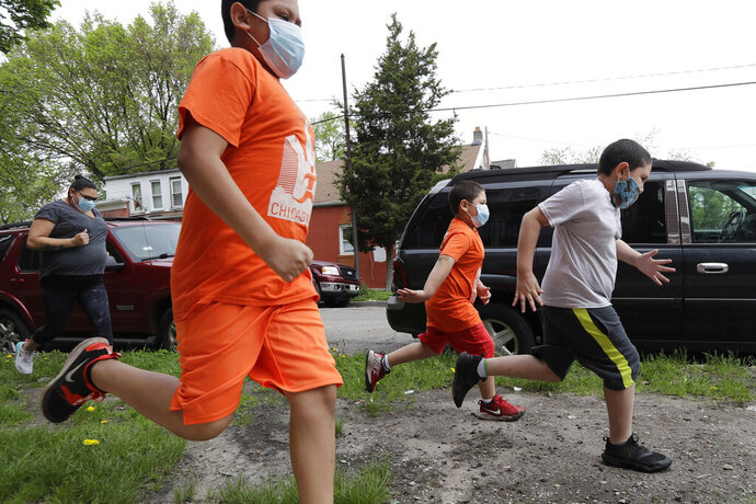 Brothers Victor Ochoa, 7, right, Jesus Ochoa, 5, second from right, Mariano Ochoa 9, second from left, and their mother Mariana Ochoa run in front of their home in Chicago, Friday, May 22, 2020.  Chicago Run's at-home fitness programs have become an essential part of the family's routine during the coronavirus pandemic. (AP Photo/Nam Y. Huh)