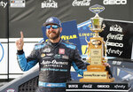 Martin Truex Jr. stands with his trophy in Victory Lane after winning the NASCAR Cup Series auto race at Darlington Raceway, Sunday, May 9, 2021, in Darlington, S.C. (AP Photo/Terry Renna)