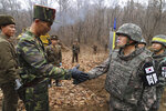 FILE - In this undated file photo provided by South Korea Defense Ministry, a South Korean soldier, right, and North Korean soldier shake hands as they meet to open a road connecting the two sides across the demilitarized zone in a project to excavate Korean War remains near the military demarcation line inside the Demilitarized Zone in Cheorwon, South Korea. With their second summit fast approaching, speculation is growing that U.S. President Donald Trump may try to persuade North Korean leader Kim Jong Un to commit to denuclearization by giving him something he wants more than almost anything else, an announcement of peace and an end to the Korean War.(South Korea Defense Ministry via AP, File)
