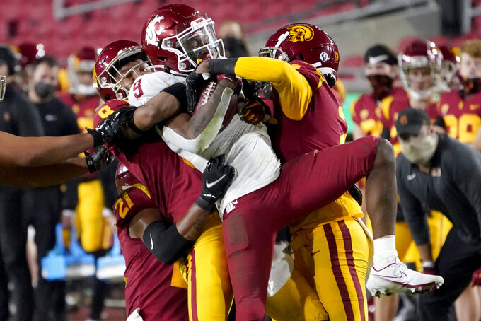 Southern California cornerback Chris Steele, left, and cornerback Olaijah Griffin, right, bring down Washington State wide receiver Renard Bell, center, after a catch during the second half of an NCAA college football game in Los Angeles, Sunday, Dec. 6, 2020. (AP Photo/Alex Gallardo)