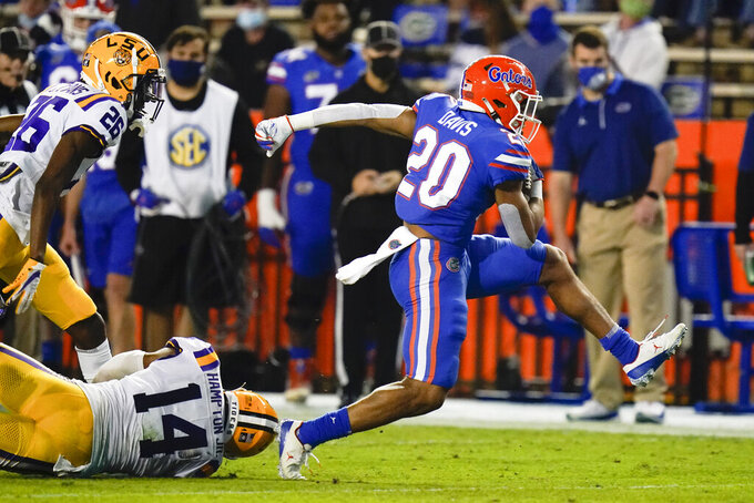 Florida running back Malik Davis (20) dashes past LSU safety Maurice Hampton Jr. (14) and cornerback Darren Evans (26) during the first half of an NCAA college football game Saturday, Dec. 12, 2020, in Gainesville, Fla. (AP Photo/John Raoux)