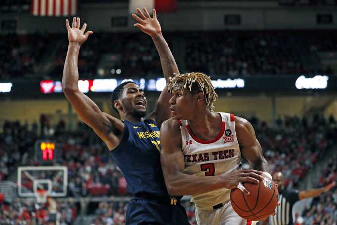 Texas Tech's Jahmi'us Ramsey (3) looks to pass the ball around West Virginia's Taz Sherman (12) during the first half of an NCAA college basketball game Wednesday, Jan. 29, 2020, in Lubbock, Texas. (AP Photo/Brad Tollefson)
