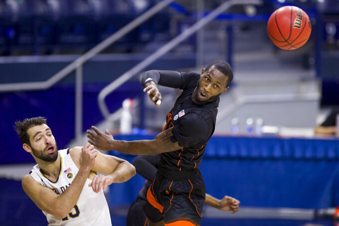 Notre Dame's Nikola Djogo (13) and Miami's Elijah Olaniyi compete for a rebound during the first half of an NCAA college basketball game Sunday, Feb. 14, 2021, in South Bend, Ind. (AP Photo/Robert Franklin)