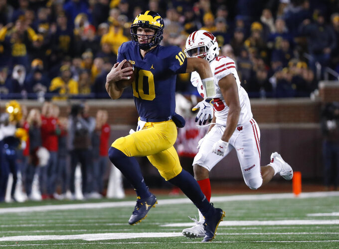 Michigan quarterback Dylan McCaffrey runs for a 44-yard touchdown against Wisconsin during the second half of an NCAA college football game in Ann Arbor, Mich., Saturday, Oct. 13, 2018. (AP Photo/Paul Sancya)