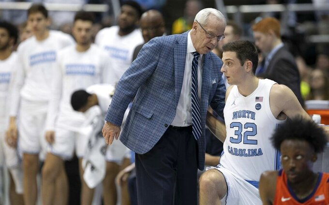 North Carolina coach Roy Williams has a word with Justin Pierce (32) as he inserts him into the game in the first half of an NCAA college basketball against Clemson game on Saturday, Jan. 11, 2020, at the Smith Center in Chapel Hill, N.C. (Robert Willett/The News & Observer via AP)