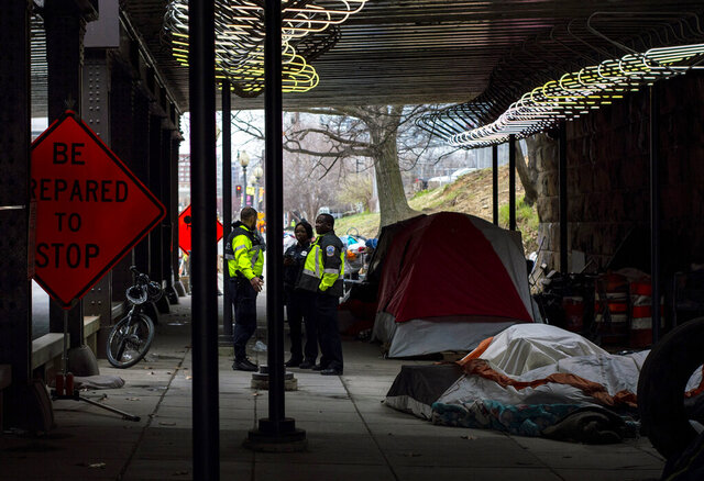 In this March 3, 2020 photo released by the University of Maryland via the Howard Center for Investigative Journalism, Washington, D.C., officials confer under a railroad overpass on L Street NE, about eight blocks from the U.S. Capitol, before garbage trucks and front loaders remove the homeless encampment there. (Susannah Outhier/University of Maryland via AP)