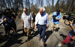 Democratic presidential candidate Sen. Bernie Sanders, I-Vermont,right, talks with area resident Michael Ranney as he tours a mobile home park that was destroyed by last year's wildfire in Paradise, Calif., Thursday, Aug. 22, 2019.  Sanders released a $16.3 trillion climate plan Thursday that builds on the Green New Deal and calls for the United States to move to renewable energy across the economy by 2050 and declare climate change a national emergency. (AP Photo/Rich Pedroncelli)
