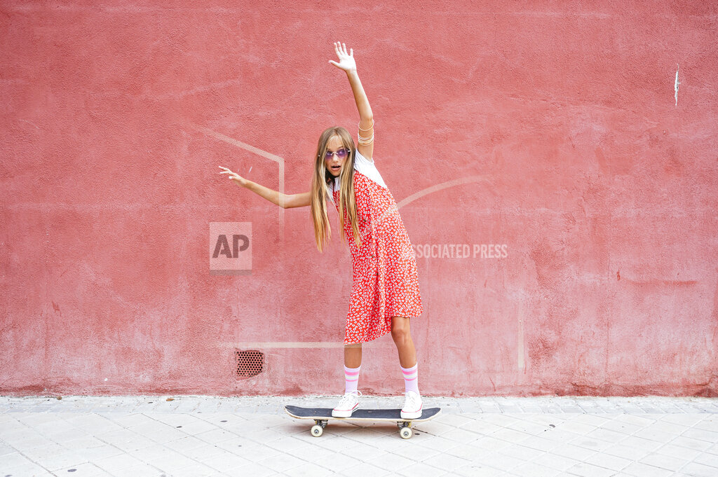 Pre-adolescent girl with hand raised skateboarding on footpath
