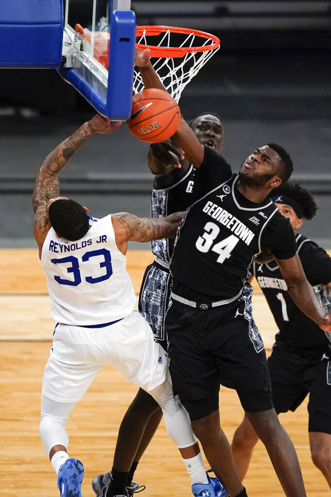 Georgetown's Qudus Wahab (34) blocks a shot by Seton Hall's Shavar Reynolds (33) during the second half of an NCAA college basketball game in the semifinals in the Big East men's tournament Friday, March 12, 2021, in New York. (AP Photo/Frank Franklin II)