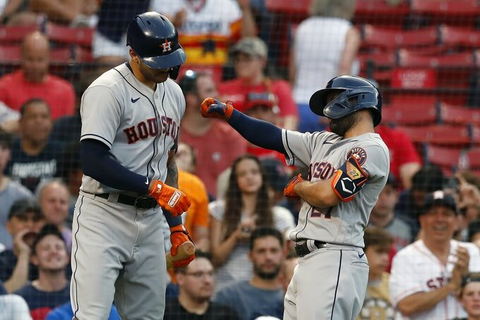 Houston Astros' Jose Altuve, right, celebrates his solo home run with teammate Carlos Correa, left, during the third inning of a baseball game against the Boston Red Sox, Wednesday, June 9, 2021, in Boston. (AP Photo/Michael Dwyer)