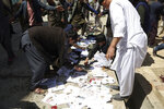 Afghans search ID papers and photos of their relatives on the ground outside a voter registration center after being attacked by a suicide bomber in Kabul, Afghanistan, Sunday, April 22, 2018. (AP Photo/Rahmat Gul)