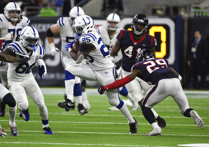 Indianapolis Colts running back Marlon Mack (25) runs past Houston Texans defensive back Andre Hal (29) during the second half of an NFL wild card playoff football game, Saturday, Jan. 5, 2019, in Houston. (AP Photo/Eric Christian Smith)