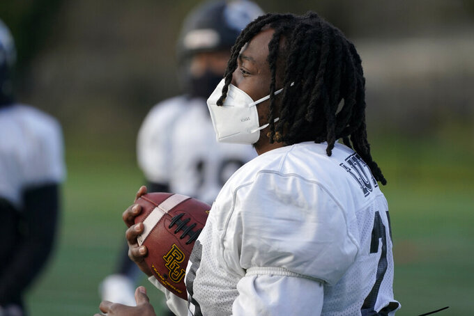 Malik White, a senior running back at Pacific Lutheran, wears a KN95 mask as he holds a football during practice Tuesday, Feb. 2, 2021, on campus in Tacoma, Wash. For all the attention heaped on the FBS level of college football last fall as it tried to play, it will not be the only college football during the 2020-21 sports calendar as a handful of NCAA Division III and NAIA programs begin some form of a winter/spring season Saturday, Feb. 6. (AP Photo/Ted S. Warren)