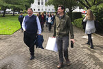Joe Emmons, right, a signature gatherer for a proposed ballot measure requiring the safe storage of weapons, and Otto Schell, legislative director of the Oregon PTA, walk with other supporters on Wednesday, Sept. 18, 2019, to the state elections office in Salem, Ore., to deliver 2,000 signatures backing the proposed ballot measure. Emmons is carrying a box containing the signatures. (AP Photo/Andrew Selsky)