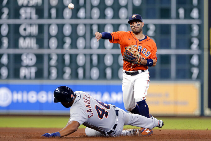 Houston Astros second baseman Jose Altuve, right, throws over Detroit Tigers' Jeimer Candelario (46) to complete a double play on Wilson Ramos during the seventh inning of a baseball game Tuesday, April 13, 2021, in Houston. (AP Photo/Michael Wyke)
