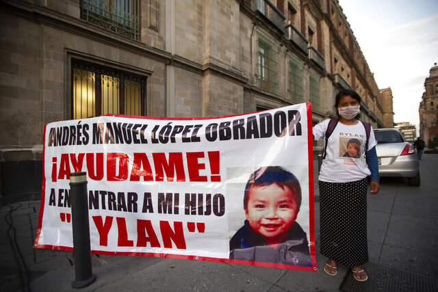 Juana Perez, whose 2 1/2 year-old son Dylan is missing, holds a poster of him outside of the presidential palace that asks for President Manuel Andres Lopez Obrador to help her find him, in Mexico City, Wednesday, July 22, 2020. The search for Perez's boy who was led away from a market in southern Mexico's Chiapas state three weeks ago led police to a horrifying discovery: 23 abducted children being kept at a house and forced to sell trinkets in the street. Pérez said officials told her that her son had not yet been found. (AP Photo/Fernando Llano)