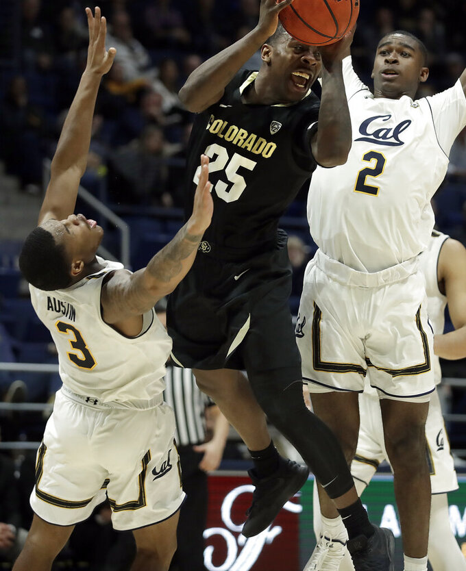 Colorado's McKinley Wright IV, center, looks to pass the ball away from California's Paris Austin (3) and Juhwan Harris-Dyson during the second half of an NCAA college basketball game Thursday, Jan. 24, 2019, in Berkeley, Calif. (AP Photo/Ben Margot)