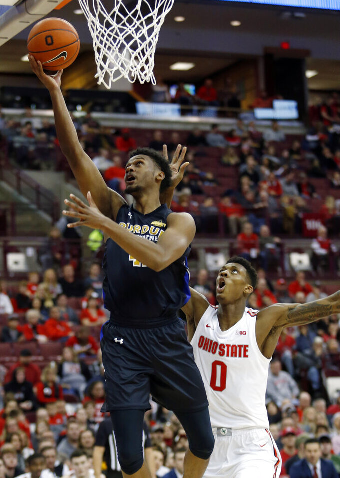 Purdue Fort Wayne guard Marcus DeBerry, left, goes up for a shot in front of Ohio State forward Alonzo Gaffney during the first half of an NCAA college basketball game in Columbus, Ohio, Friday, Nov. 22, 2019. (AP Photo/Paul Vernon)