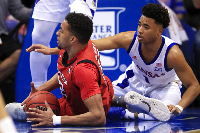 Texas Tech forward TJ Holyfield (22) controls the ball in front of Kansas guard Devon Dotson (1) during the first half of an NCAA college basketball game in Lawrence, Kan., Saturday, Feb. 1, 2020. (AP Photo/Orlin Wagner)
