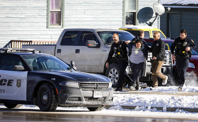 A woman in hand cuffs is lead from the scene were shots were fired at 812 5th Street on Tuesday, Nov. 12, 2019 in Rapid City.  Tactical officers responded to a home near downtown Rapid City after someone fired a gun from a car into a first-floor bedroom. Police say no one was hurt in Tuesday's shooting near Rapid City High School.  (Adam Fondren/Rapid City Journal via AP)